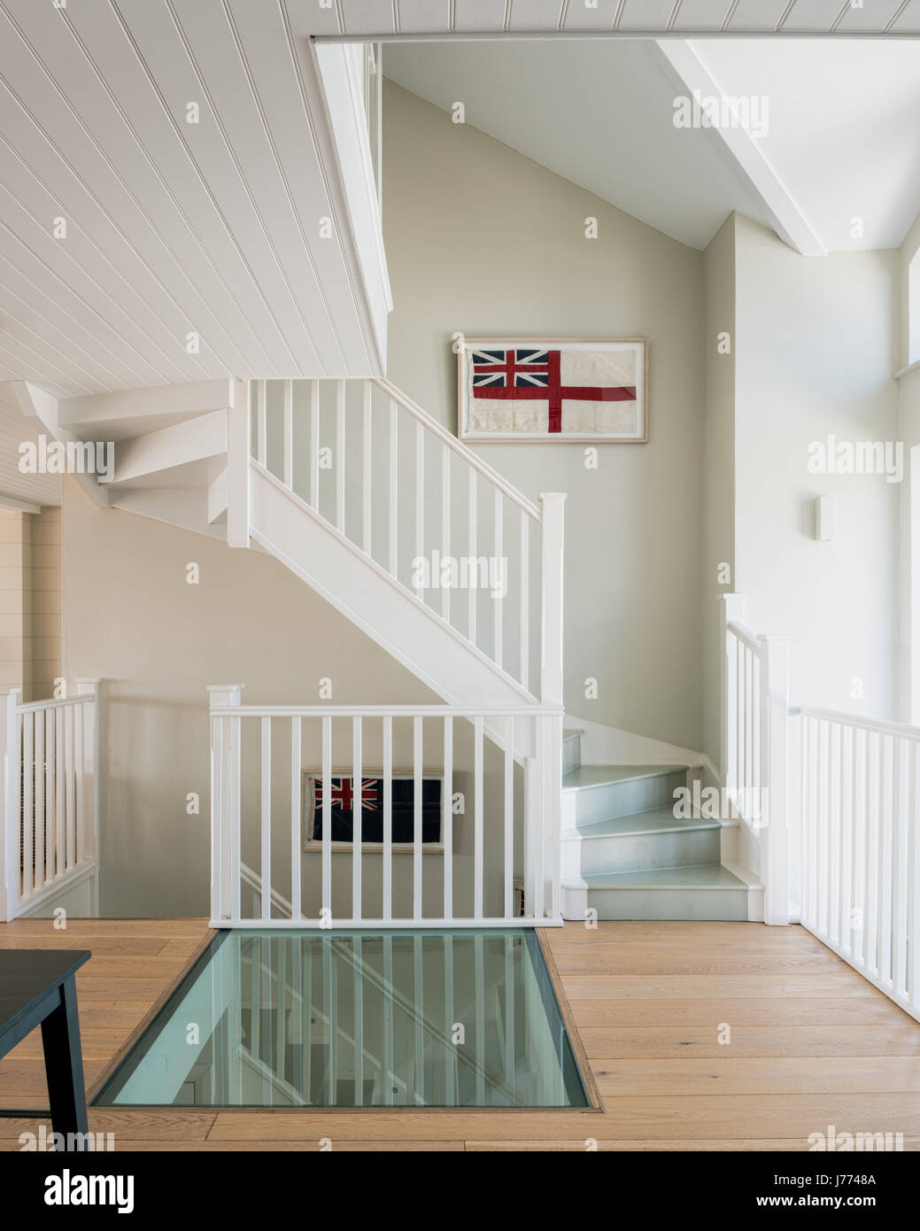 Glass floor on first storey landing with framed old british flags ...