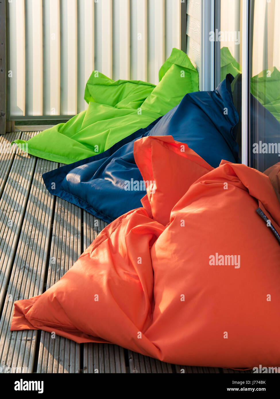 Brightly coloured bean bags on the wooden balcony - Stock Image