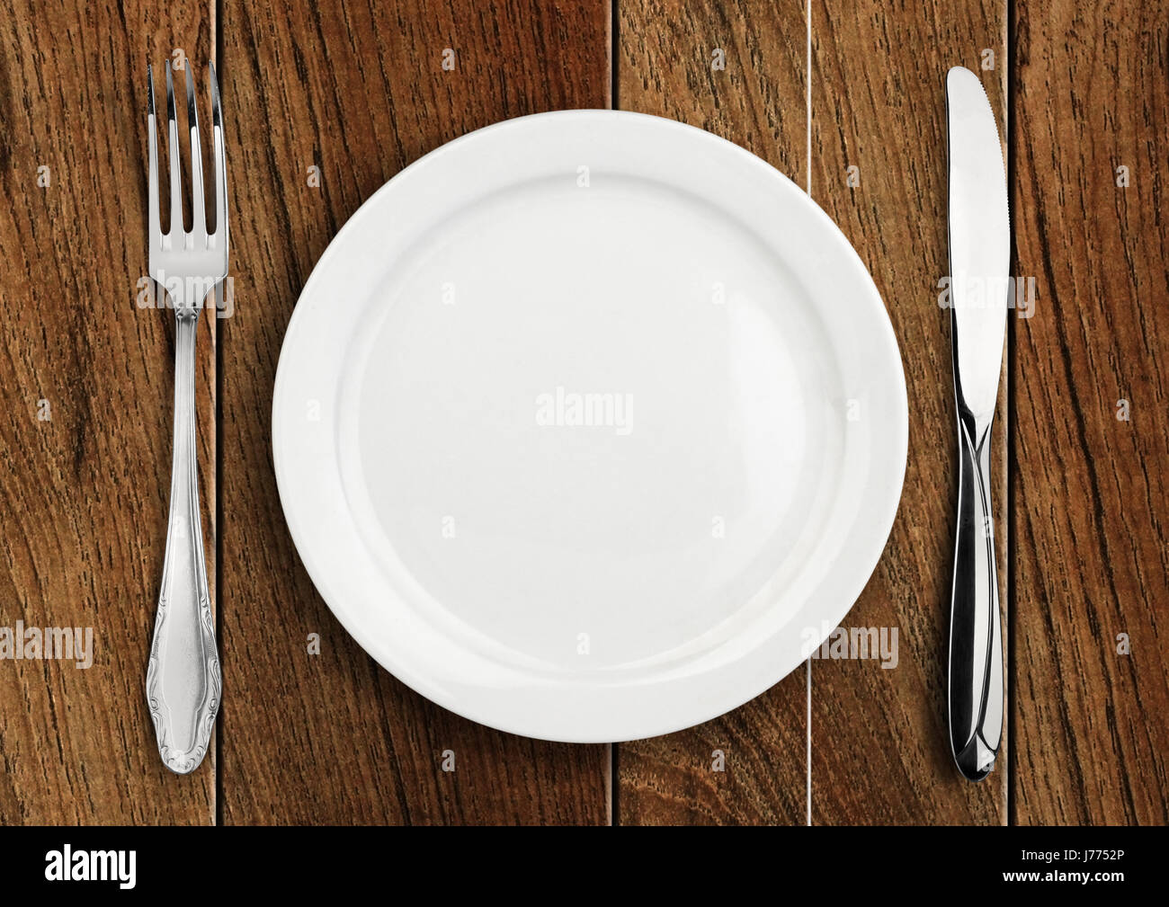 Table setting, empty plate and silverware on wooden table Stock ...