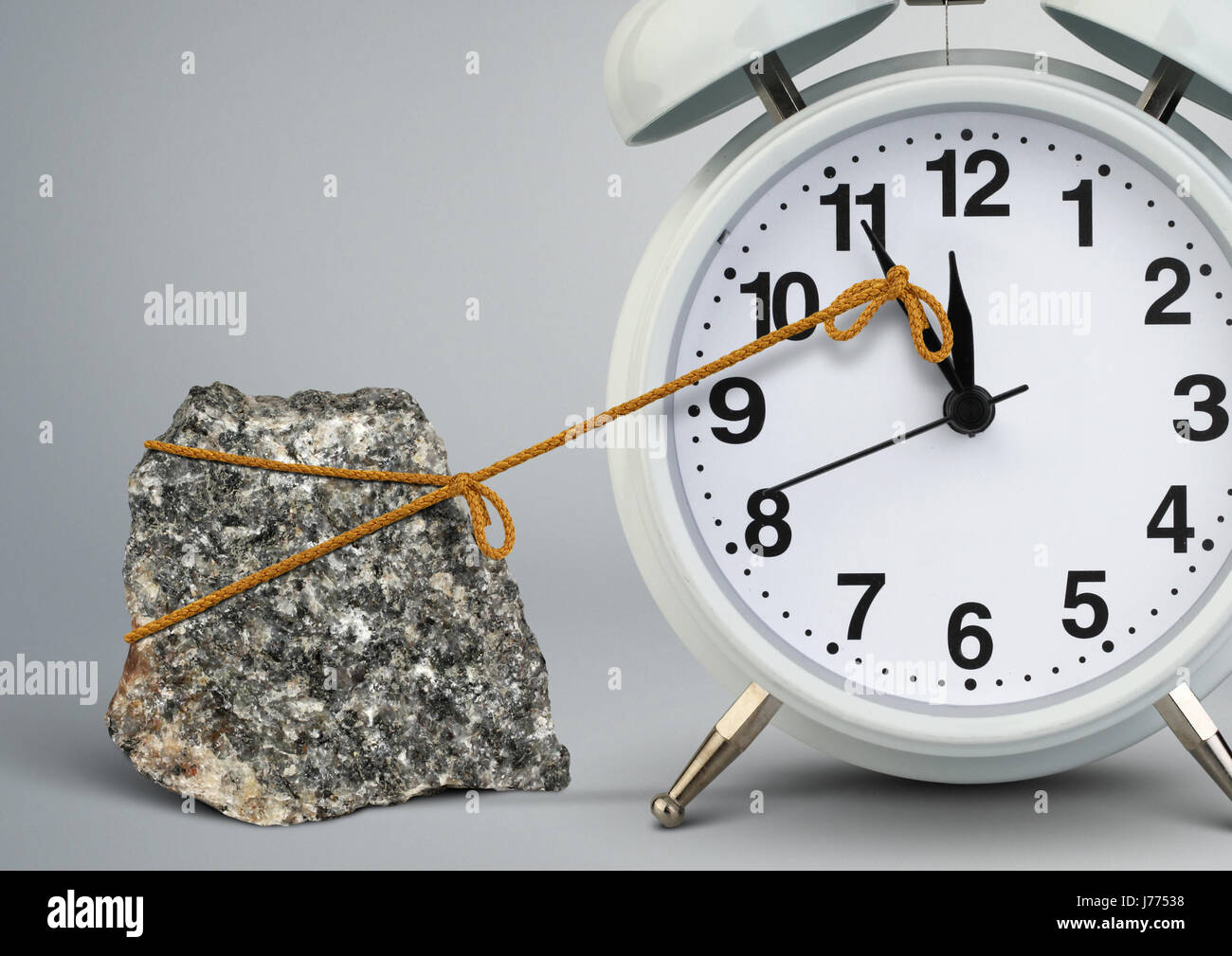 Time on clock stop by stone, delay concept - Stock Image