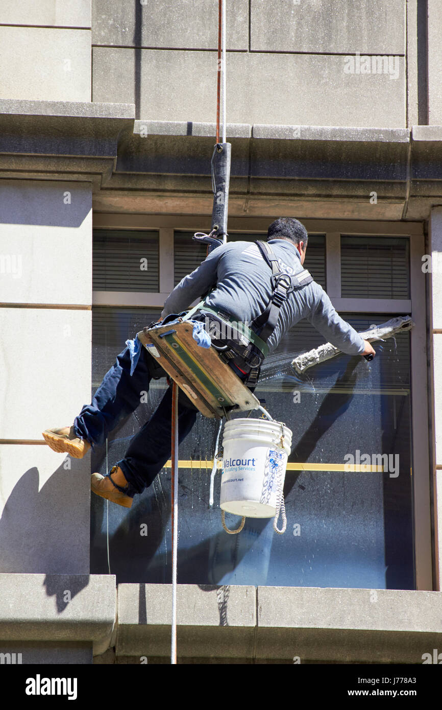 man cleaning windows using abseil rope techniques Washington DC USA Stock Photo