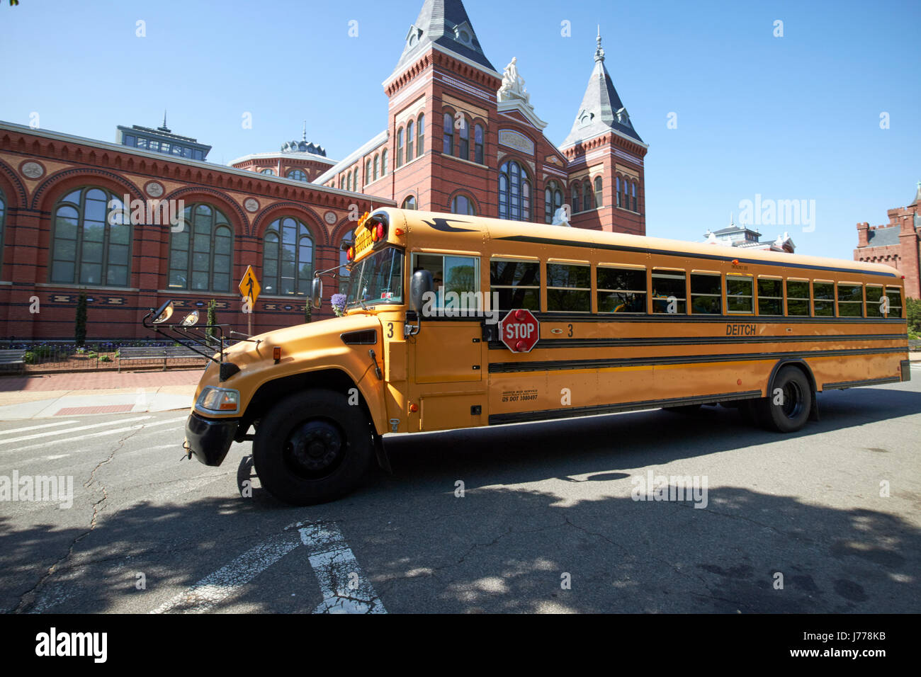 bluebird yellow school bus passing the smithsonian arts and industries building Washington DC USA - Stock Image