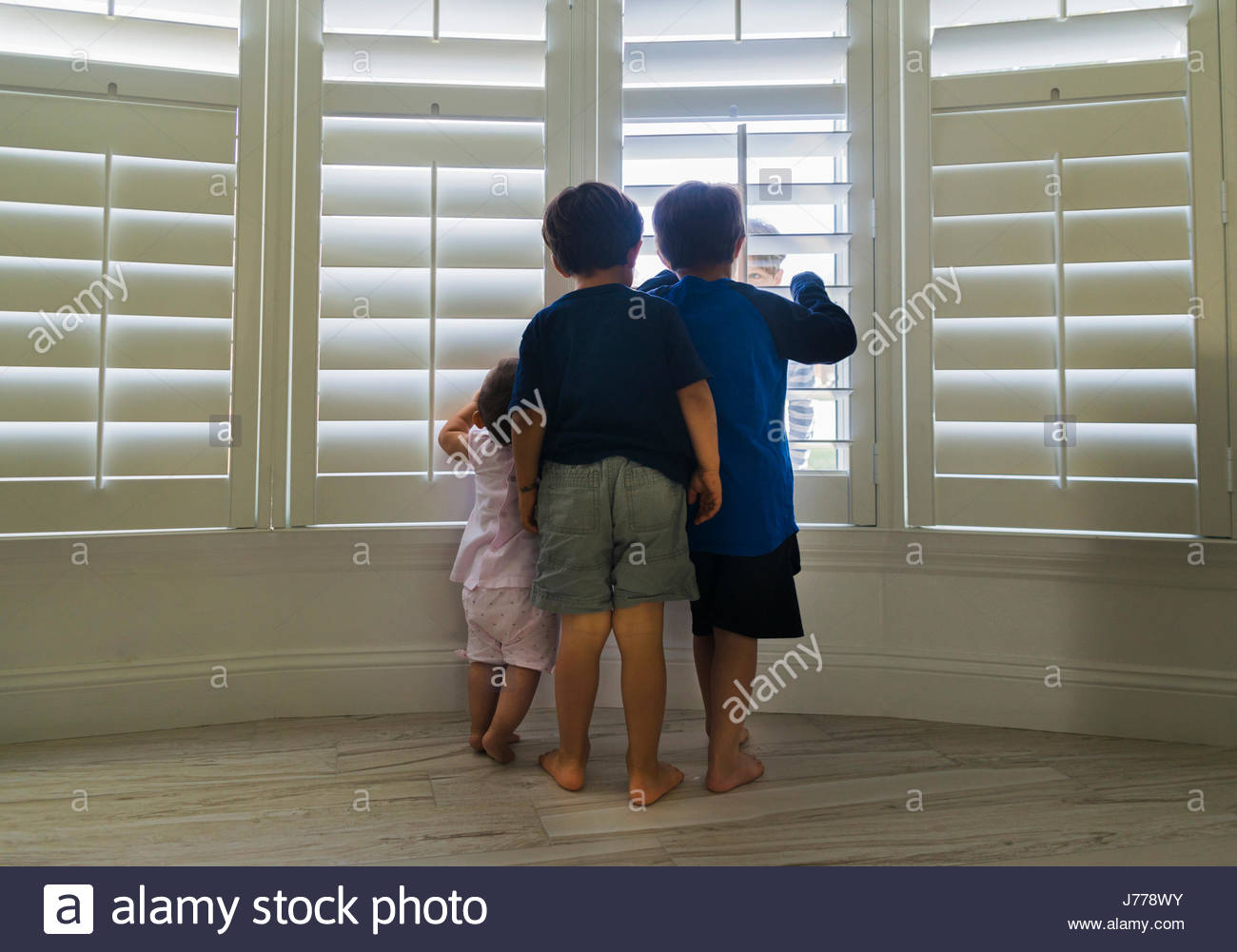 Siblings looking through window blinds at home - Stock Image