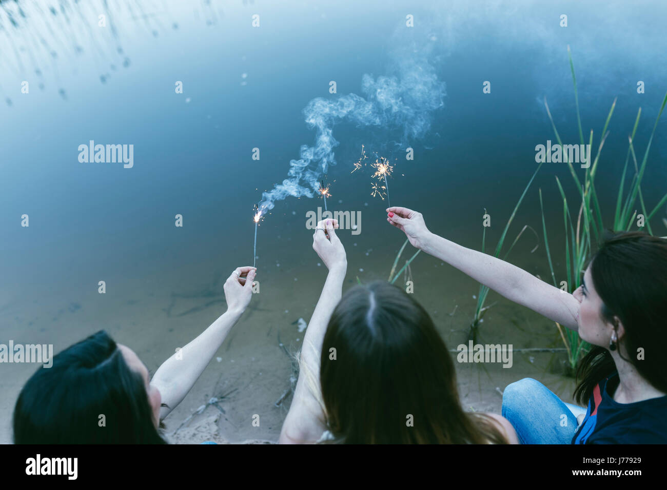 High angle view of female friends burning sparklers at lakeshore - Stock Image