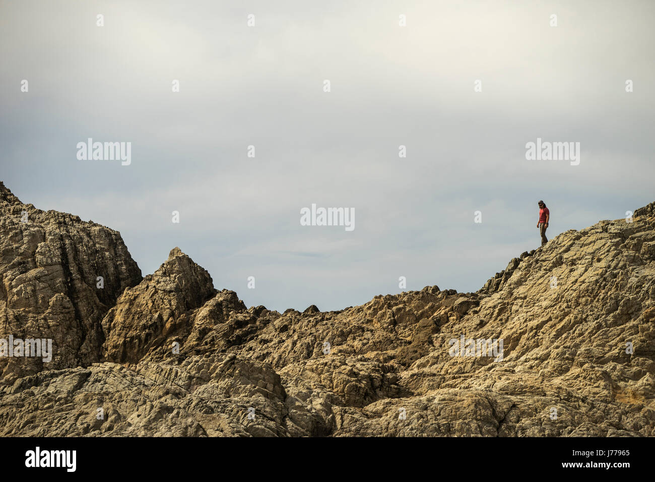 Mid distance view of man walking on mountain against sky - Stock Image