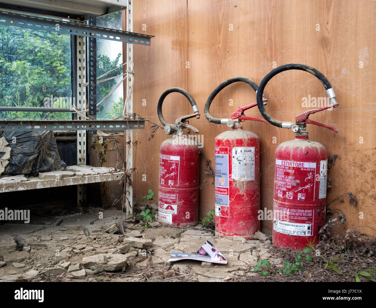 Abandoned and forgotten fire extinguishers in old building. Italy. - Stock Image