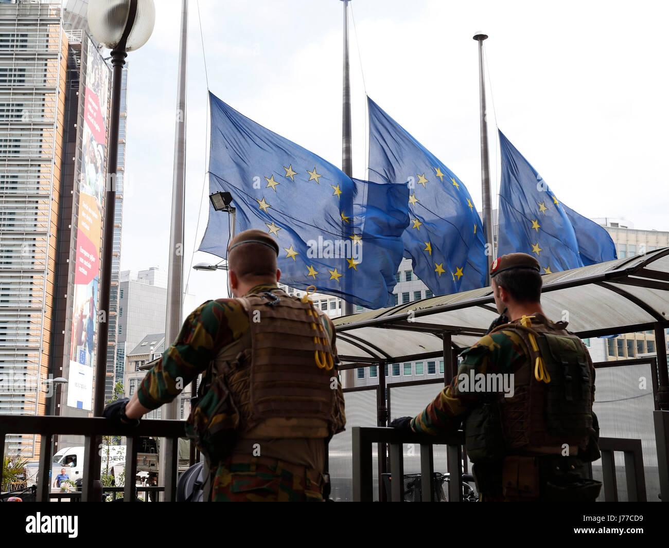 Brussels, Belgium. 23rd May, 2017. European Union flags are lowered to half mast as soldiers guard outside the European - Stock Image