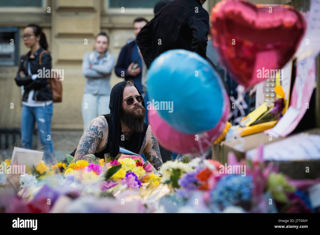 Manchester, UK. 23rd May, 2017. A man leaves flowers at St Anns Square, Manchester after a vigil was held in solidarity after an attack on Manchester Arena the night before which claimed 22 lives and injured 59. Credit: Andy Barton/Alamy Live News Stock Photo