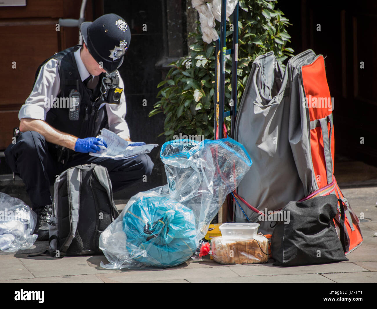 London, UK. 24th May, 2017.  An angry black homeless man is cuffed and his belongings searched - Armed police seal - Stock Image