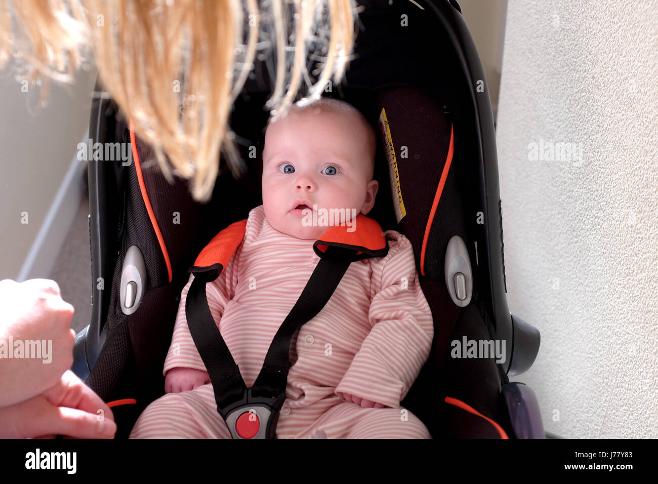 baby girl looking up strapped into a convertible car seat - Stock Image