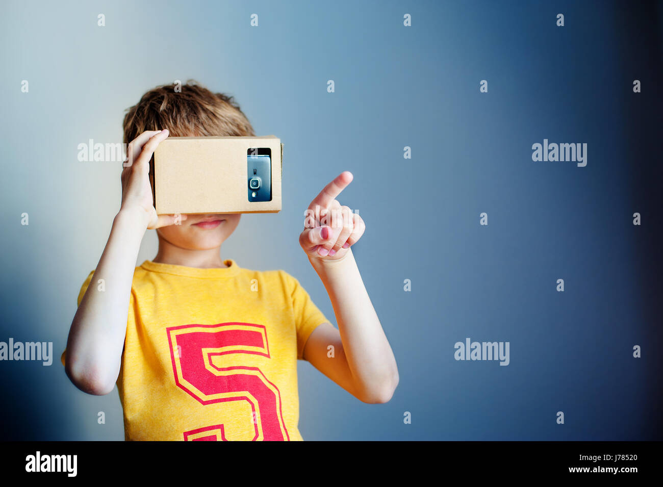 Little child uses virtual reality VR cardboard on blue background - Stock Image