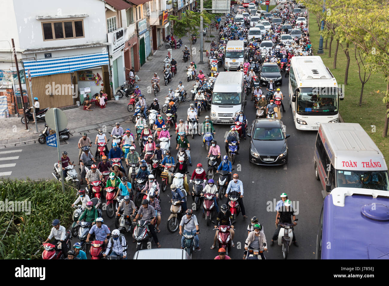 HO CHI MINH CITY, VIETNAM - Large number of motorcycles drives around cars in the busy street of Ho Chi Minh City, - Stock Image