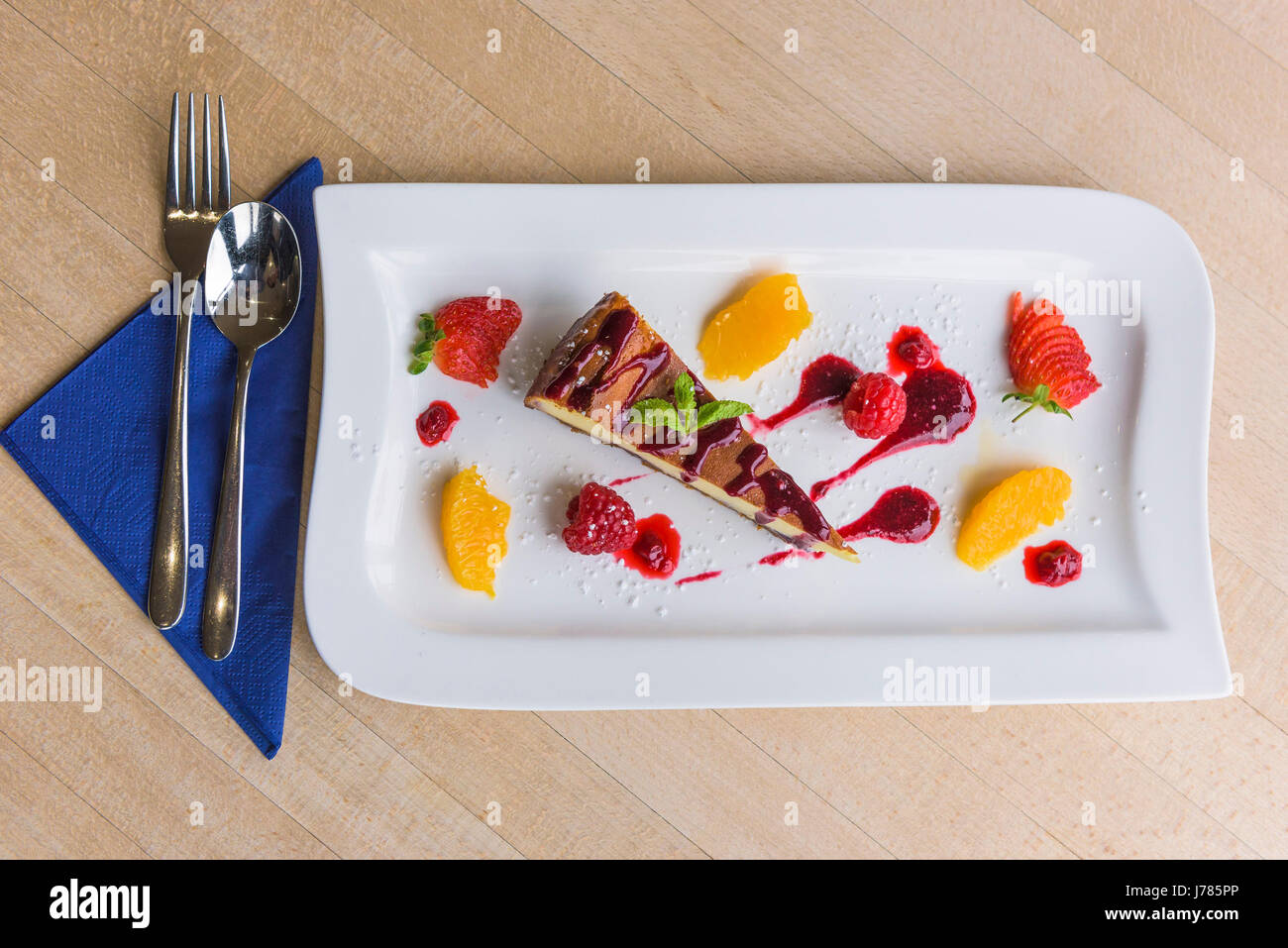 A closeup view of a colourful dessert served in a restaurant; Food; Sweet; Pudding; Cheesecake; Fruit; Tasty; Attractive - Stock Image