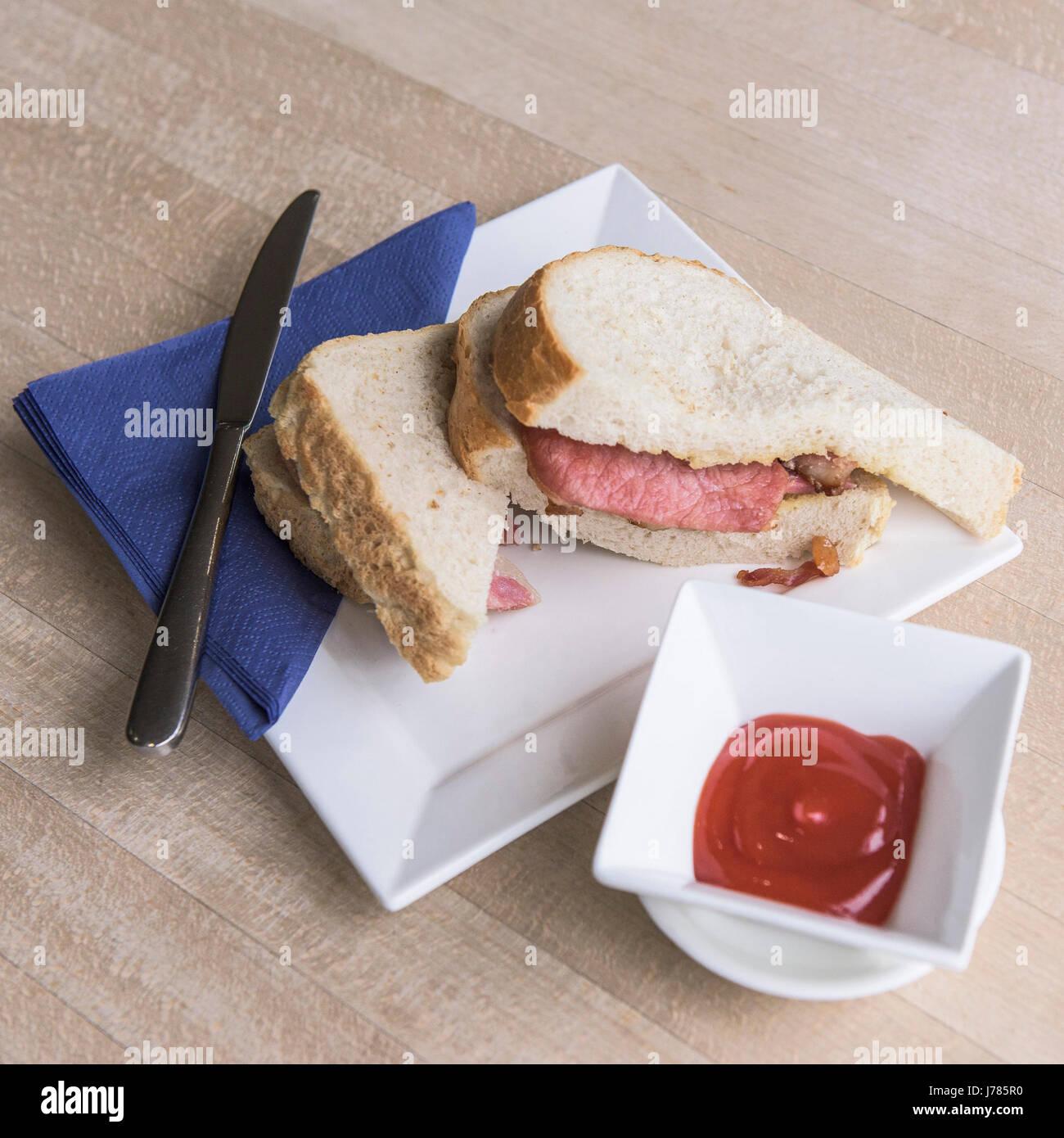 A bacon sandwich; Food; White bread; Bacon rashers; Ketchup; Plate; Knife; Napkin; - Stock Image