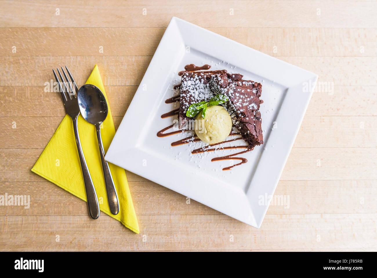 Chocolate brownies with vanilla ice cream; Pudding; Sweet; Restaurant interior; Food; Indulgence; Luxury; Luxurious; - Stock Image