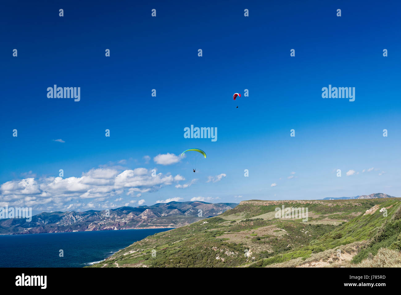 Colorful hang glider in sky over blue sea - Stock Image