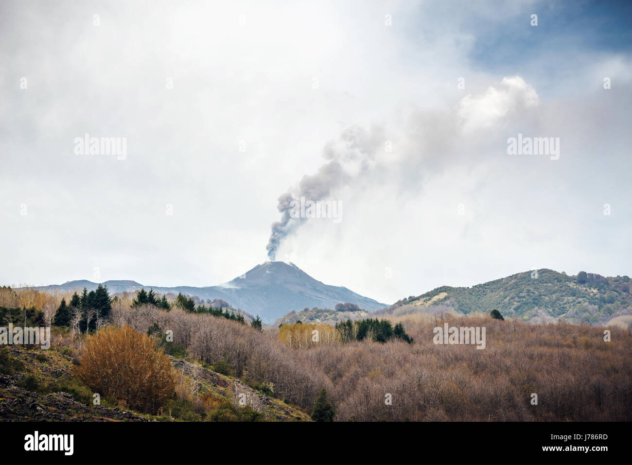 Mount Etna erupting in Sicily with clouds of ash, fields in foreground - Stock Image