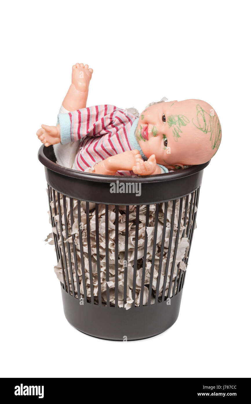 Old doll in the trash can - Stock Image