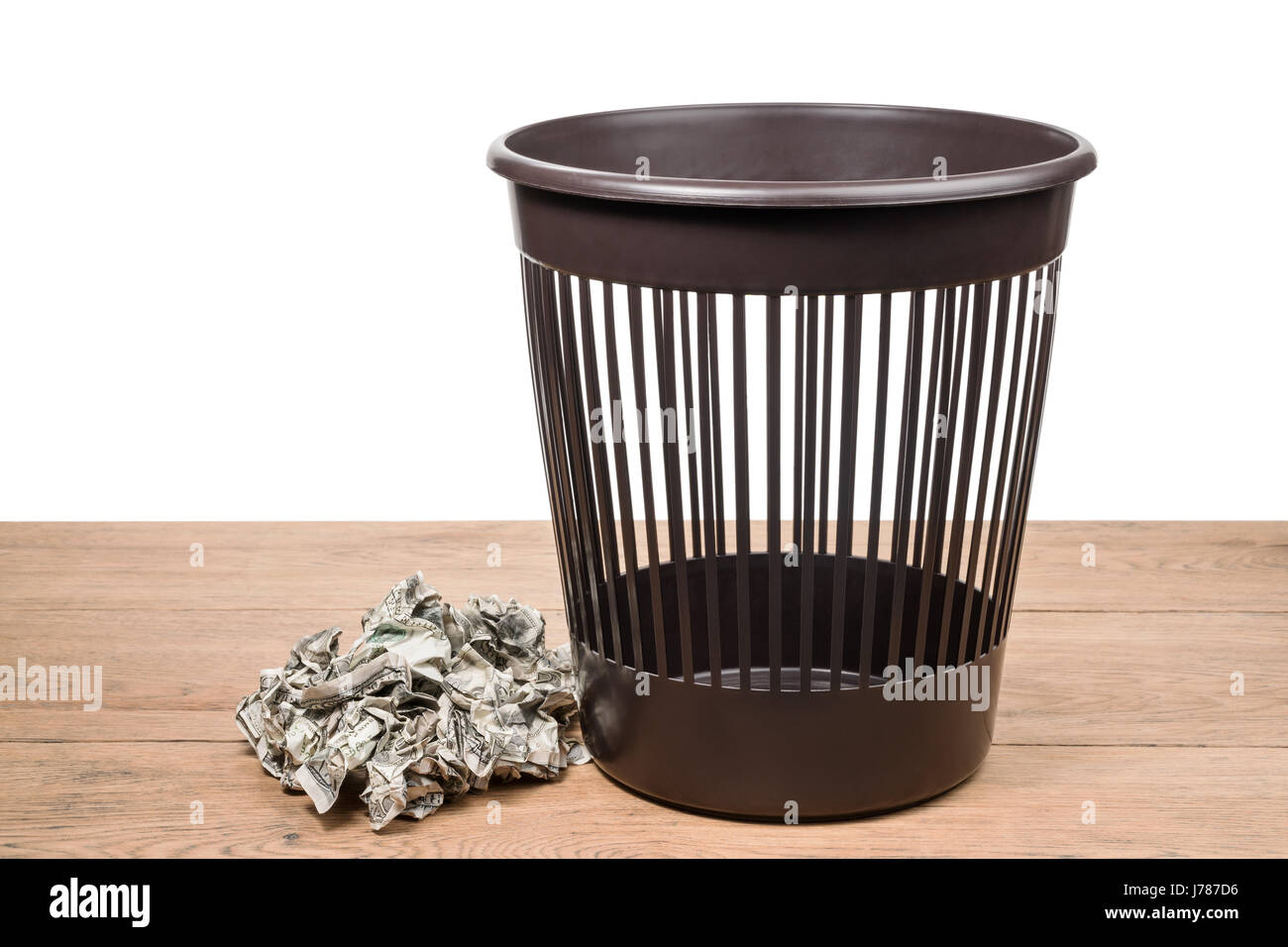 Pile of crumpled money and wastebasket Stock Photo