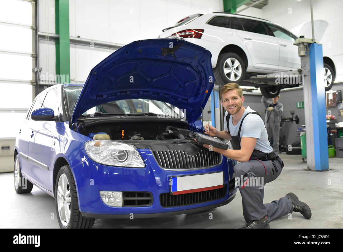 Car mechanic in a workshop using diagnostics computer at car - Stock Image