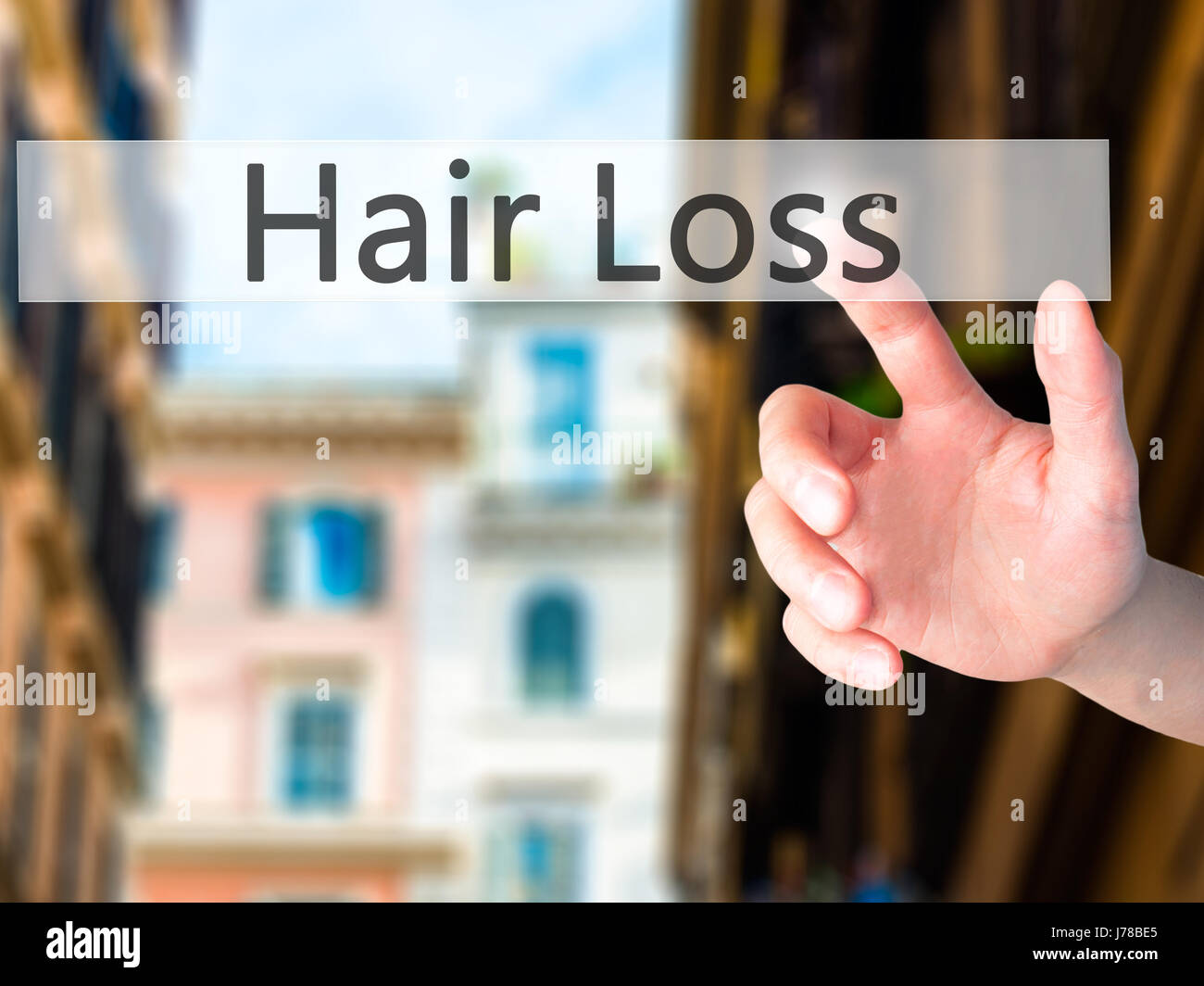 Hair Loss - Hand pressing a button on blurred background concept . Business, technology, internet concept. Stock Stock Photo
