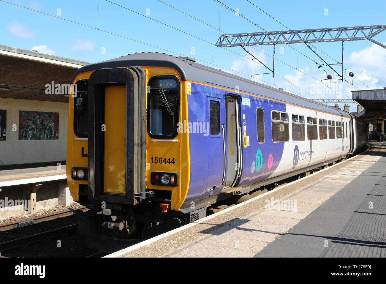 Class 156 super sprinter diesel multiple unit in the new Northern livery at platform 1 at Carnforth railway station - Stock Image