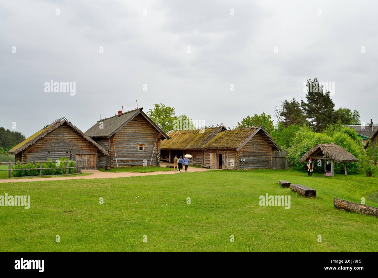 Tourists visiting the old log house in the Pushkin Mikhailovskoe summer cloudy day - Stock Image