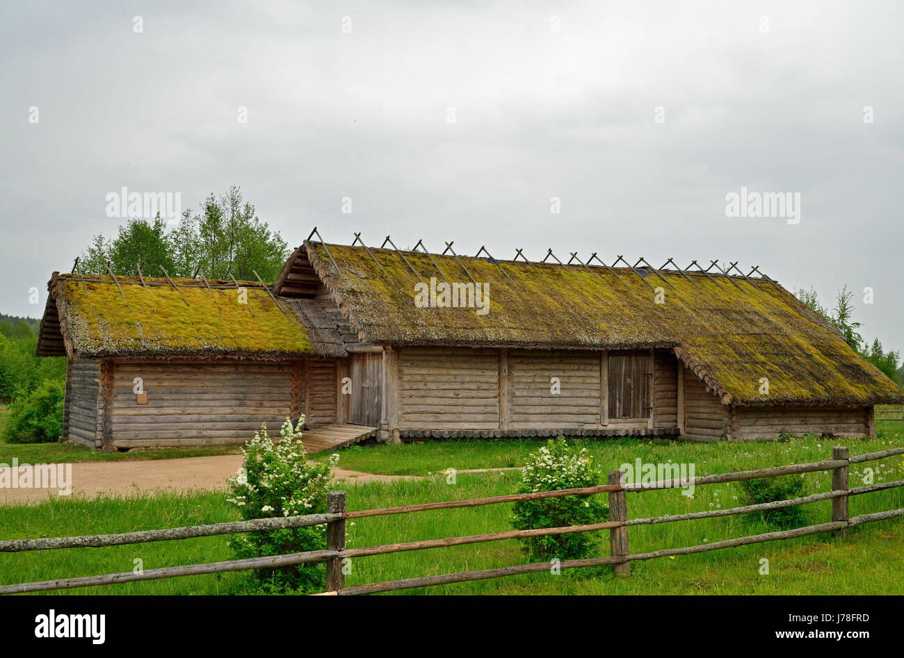 Old wooden log barn in the Museum of Pushkin Mikhailovskoe village summer cloudy day - Stock Image