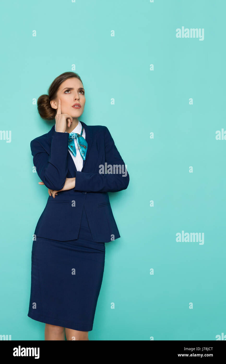 Focused young businesswoman in blue suit and turquoise scarf is holding hand on chin, looking up and thinking. Three - Stock Image