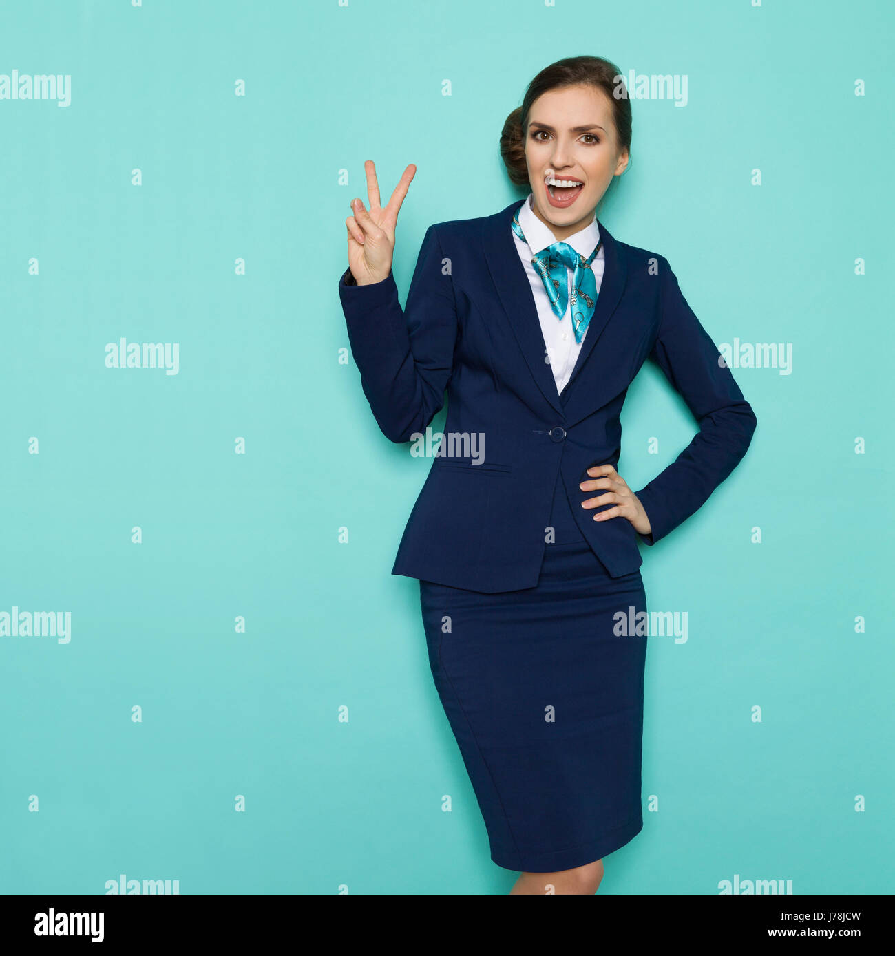 Happy stewardess in blue formal wear is showing peace hand sign, shouting and looking at camera. Three quarter length - Stock Image