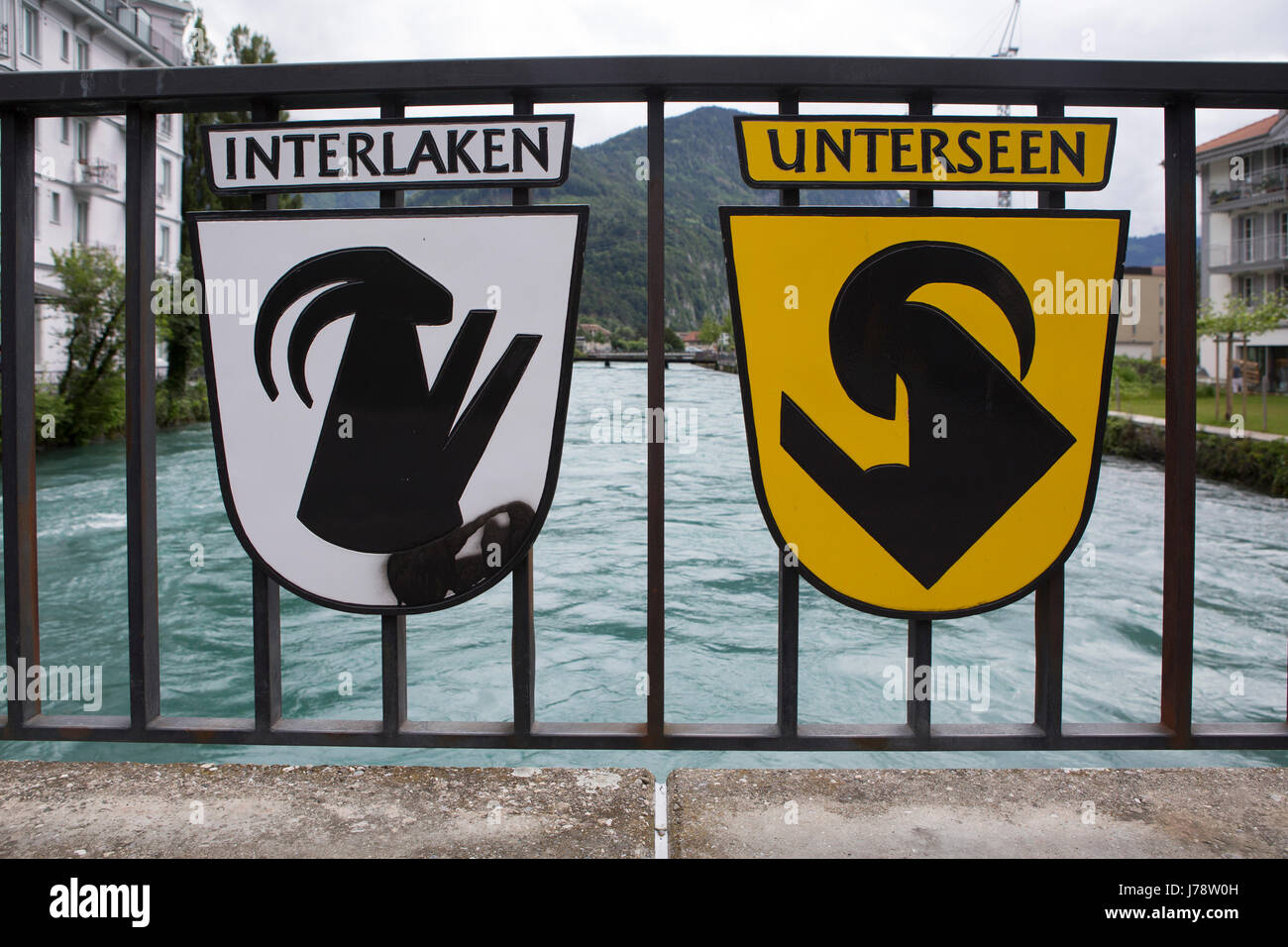 The coats of arms of Interlaken and Unterseen in Switzerland. The two municipalities are separated by the River - Stock Image