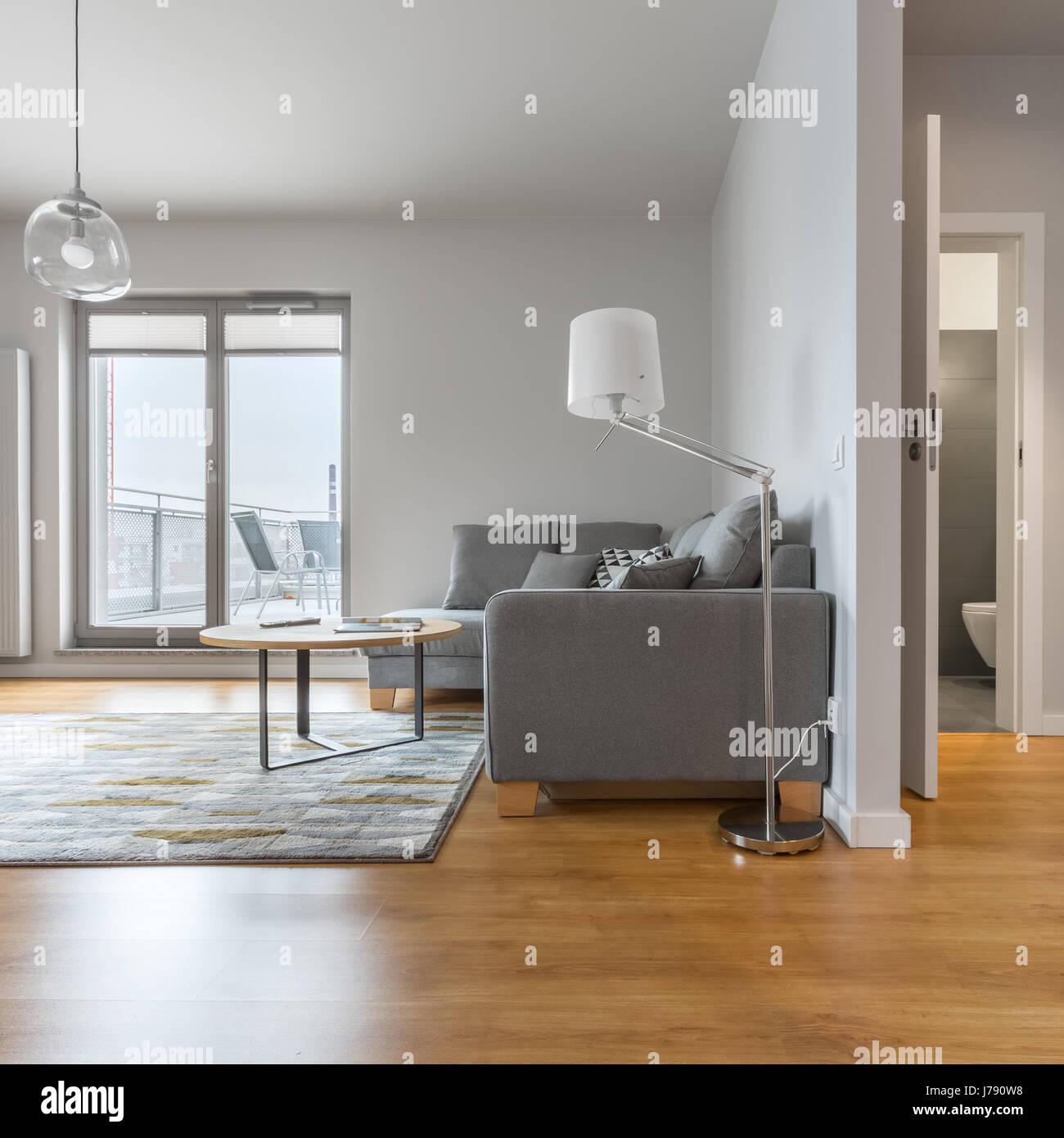 Modern living room with big window, next to hallway and bathroom doors open - Stock Image
