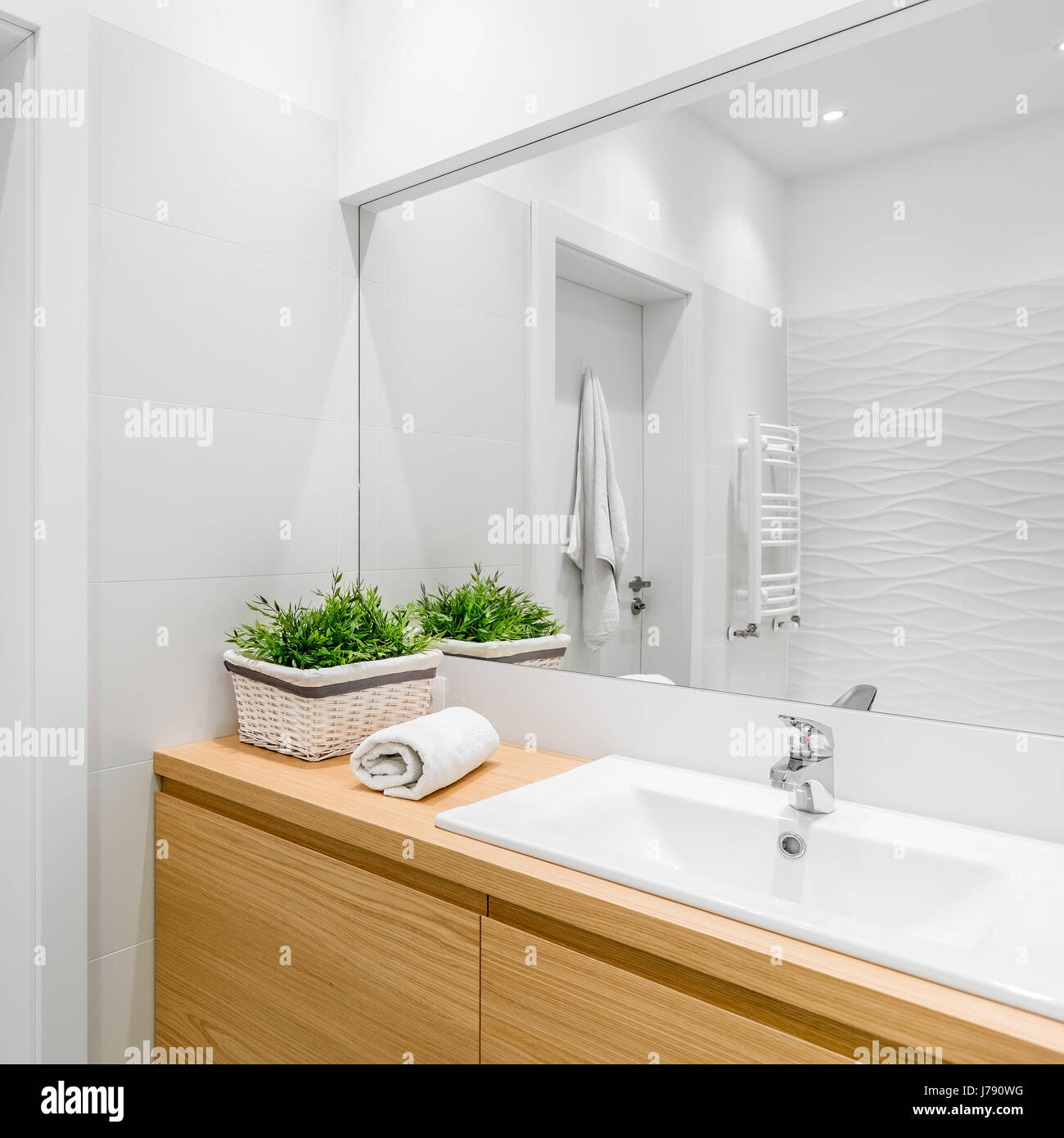 Bright bathroom with structural white tiles, wooden cabinet and big ...