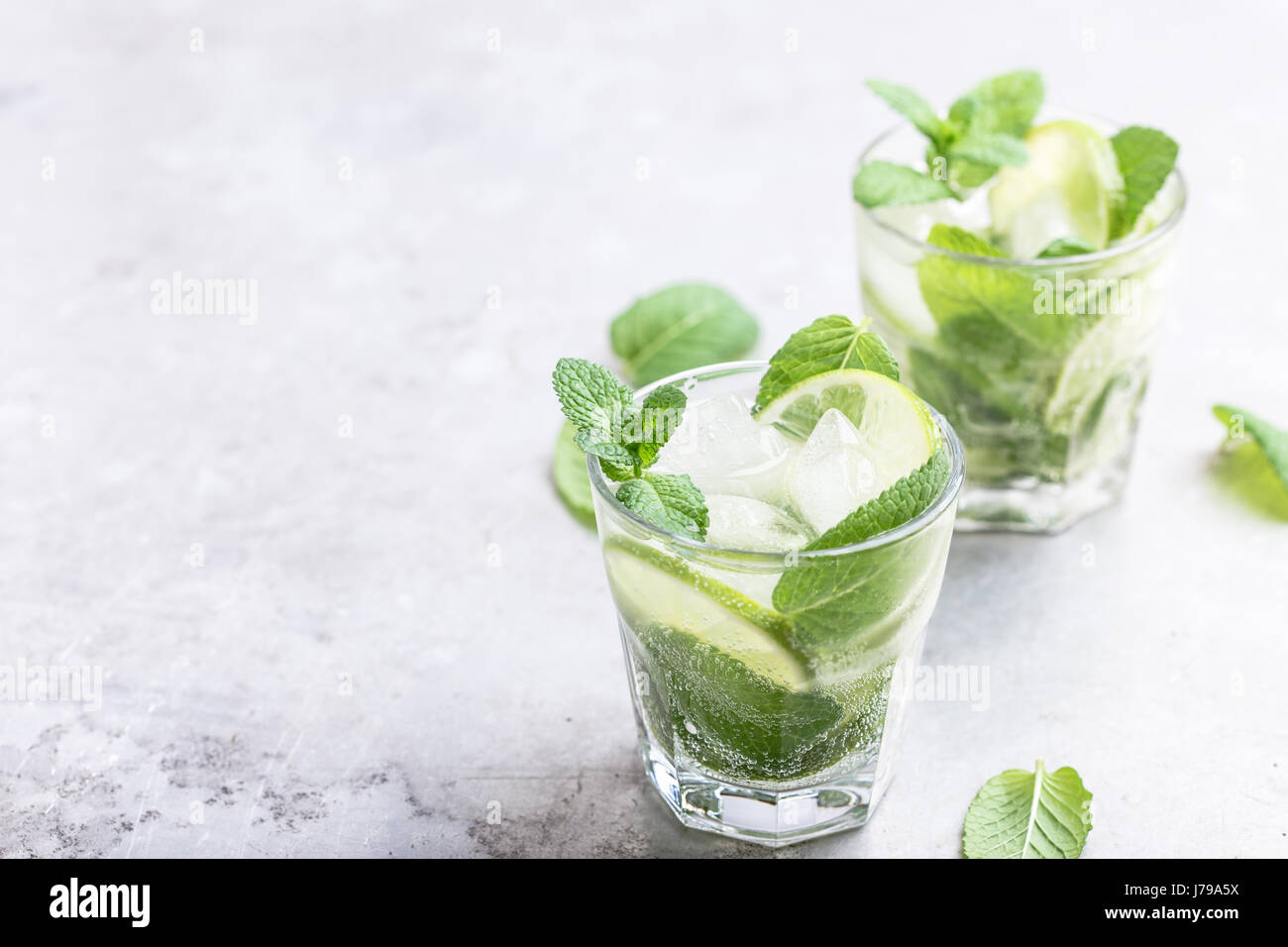 Mojito cocktail on light gray background close up, refreshing summer drink - Stock Image