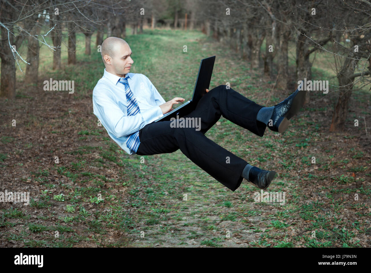 Man flying in the air. In his hands he is holding a laptop. - Stock Image