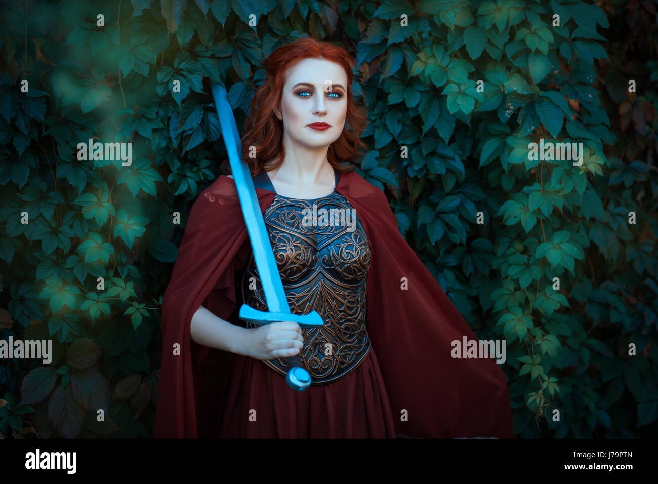 Woman warrior with sword wearing a cuirass. On the shoulders of her cloak. Stock Photo