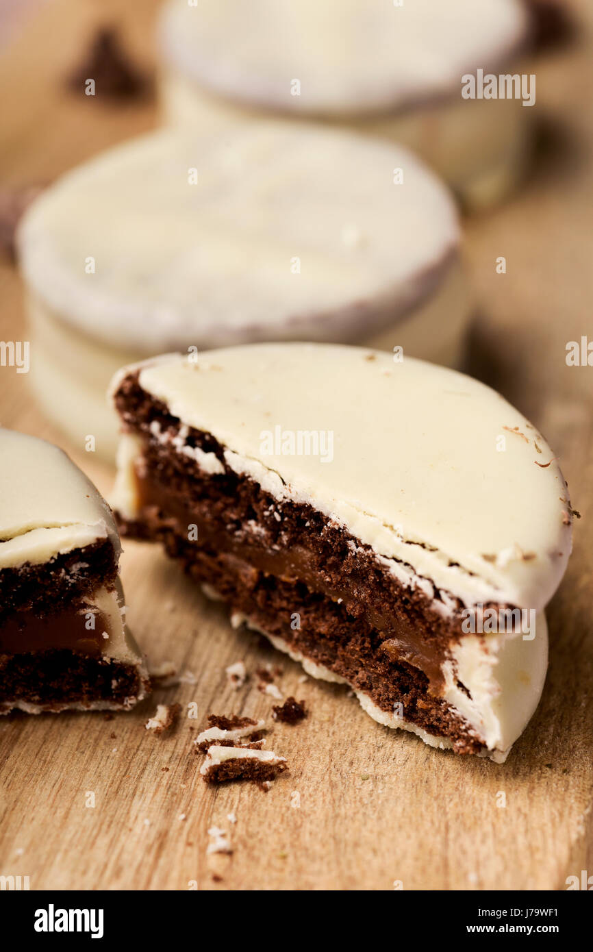 closeup of some argentinean-uruguayan alfajores filled with dulce de leche and coated with a white coating on a - Stock Image