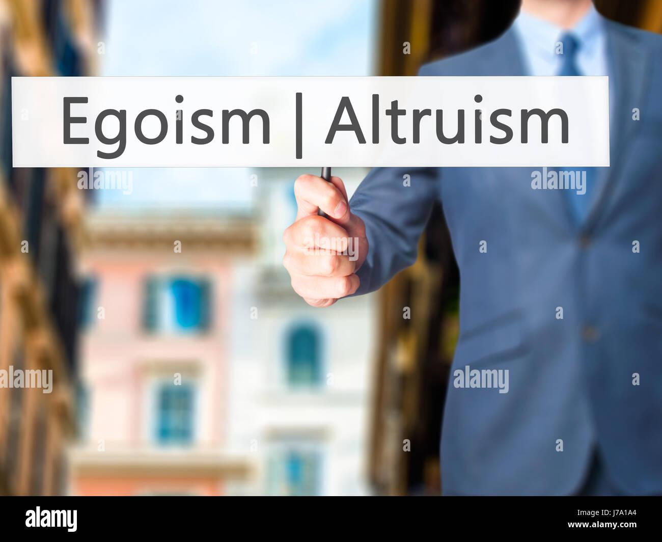 Altruism  Egoism - Businessman hand holding sign. Business, technology, internet concept. Stock Photo - Stock Image