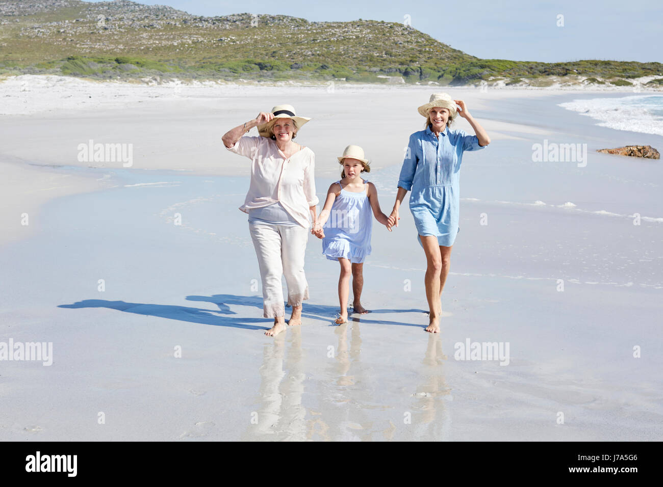 Mother, daughter and grandmother walking by the sea - Stock Image