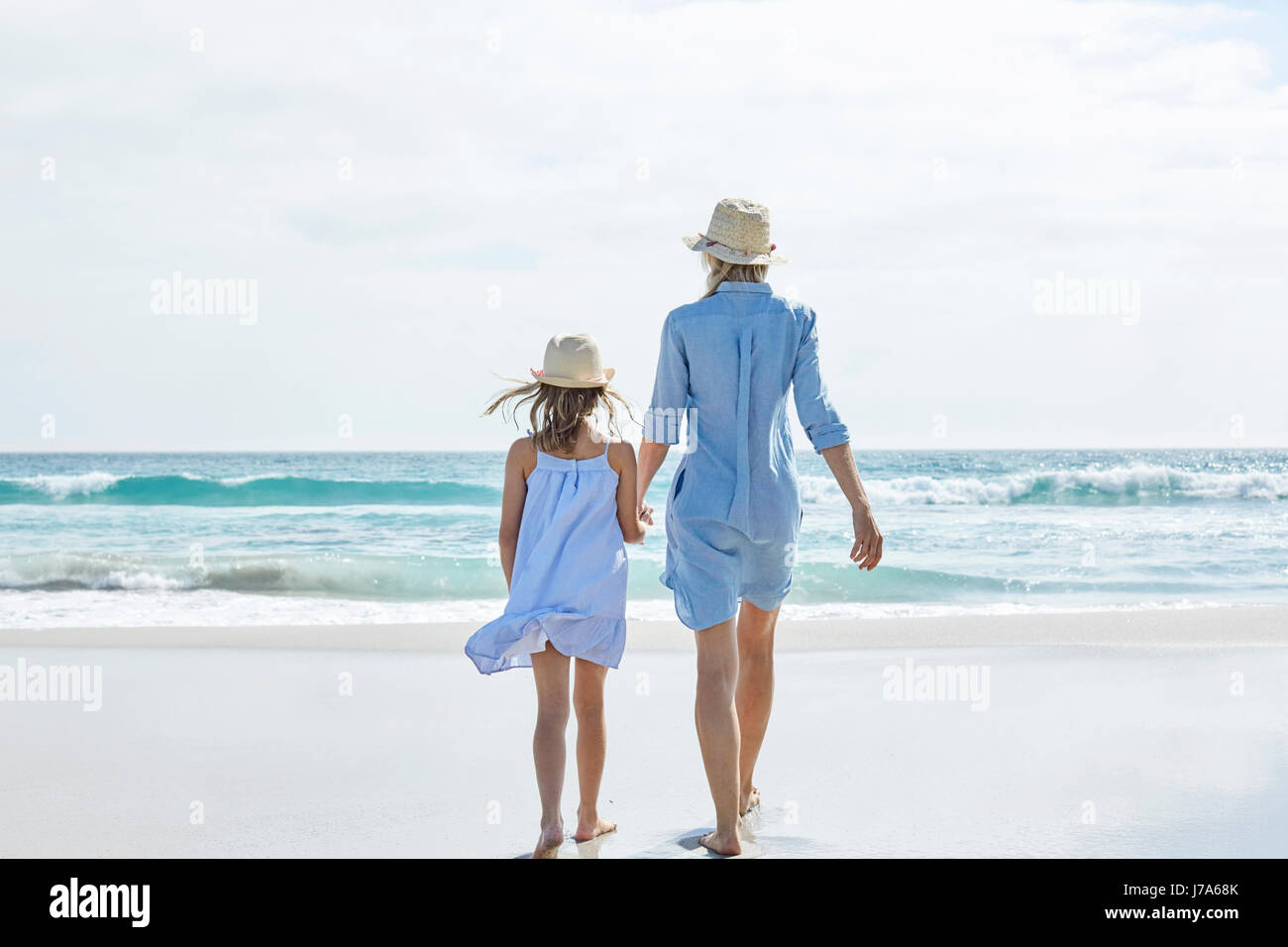 Mother and daughter walking by the sea, rear view - Stock Image
