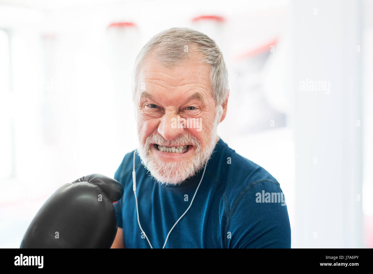 Portrait of aggressive senior man with earphones and boxing gloves in gym - Stock Image