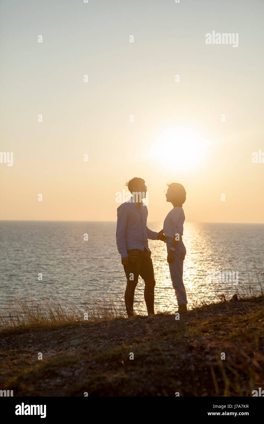 silhouette photography of couples younger man and woman standing against sun set sky - Stock Image