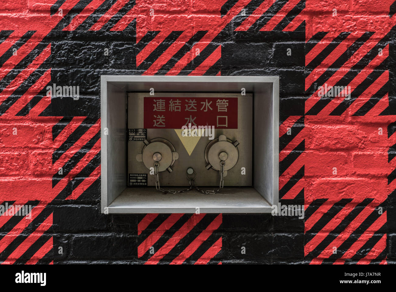 Photo of a resistant key lock box built in a red and black outdoor wall of a building in Harajuku. - Stock Image
