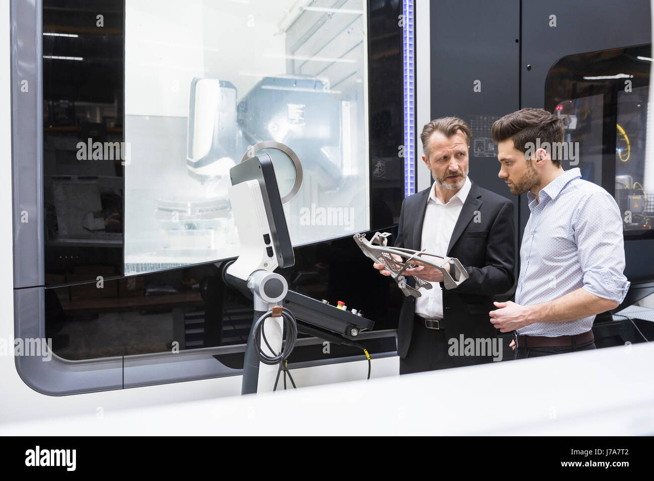 Two men in modern factory talking about a product - Stock Image