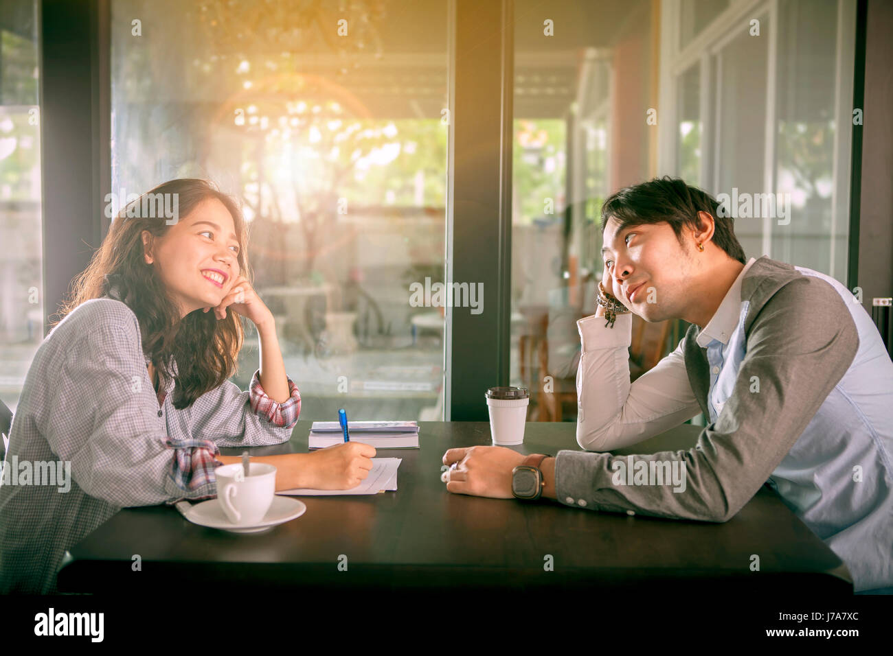 couples of younger asian man and woman relaxing with hot coffee drink in coffee shop  happiness feeling - Stock Image