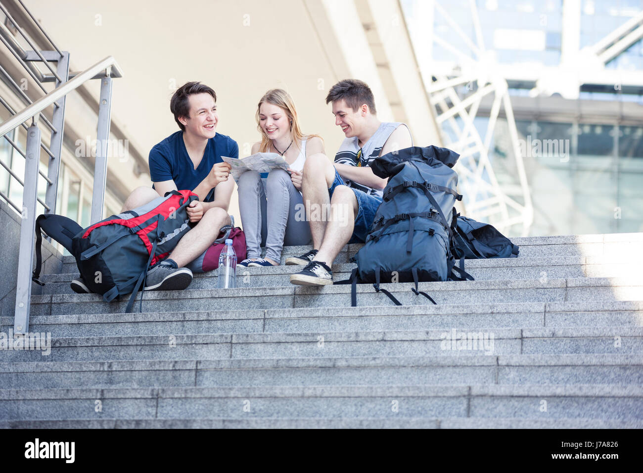 Young people exploring Berlin, looking at map - Stock Image