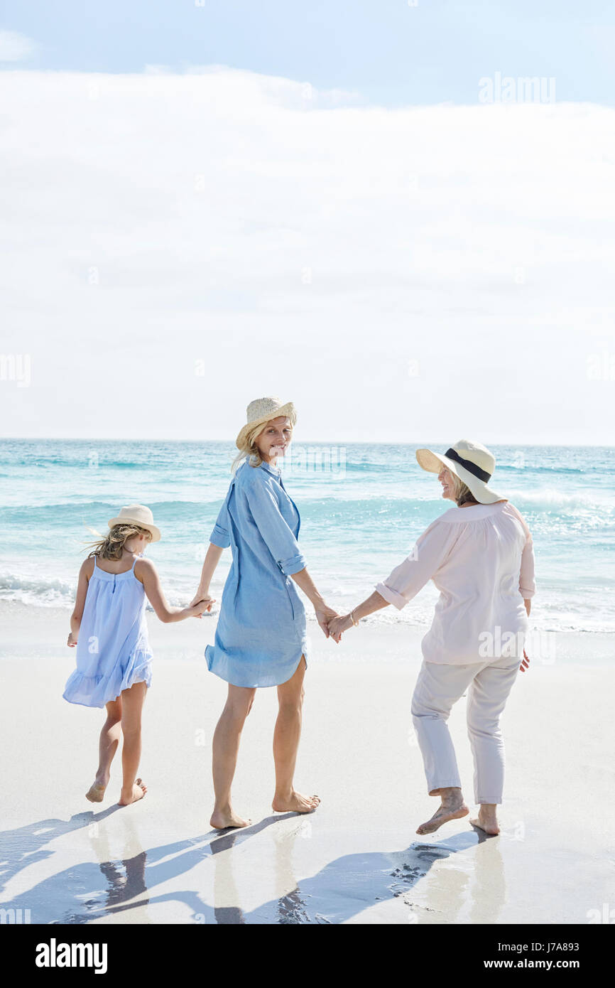 Mother, daughter and grandmother walking by the sea, rear view - Stock Image