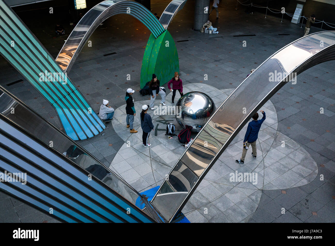 A group of teenagers practice their hip hop moves, while observing their reflection on the sphere in the centre - Stock Image