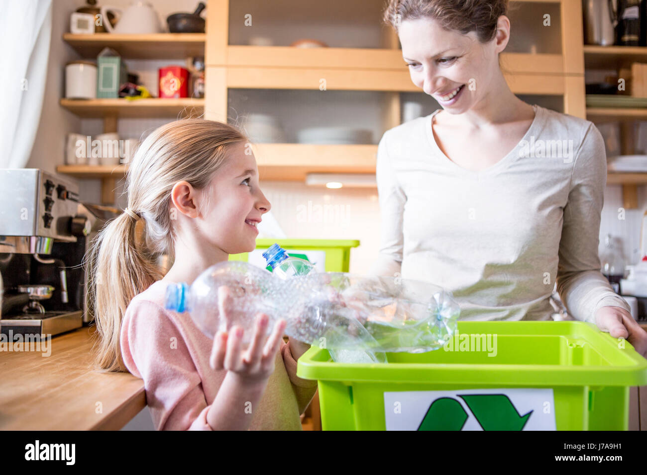 Mother and daughter at home separating waste - Stock Image