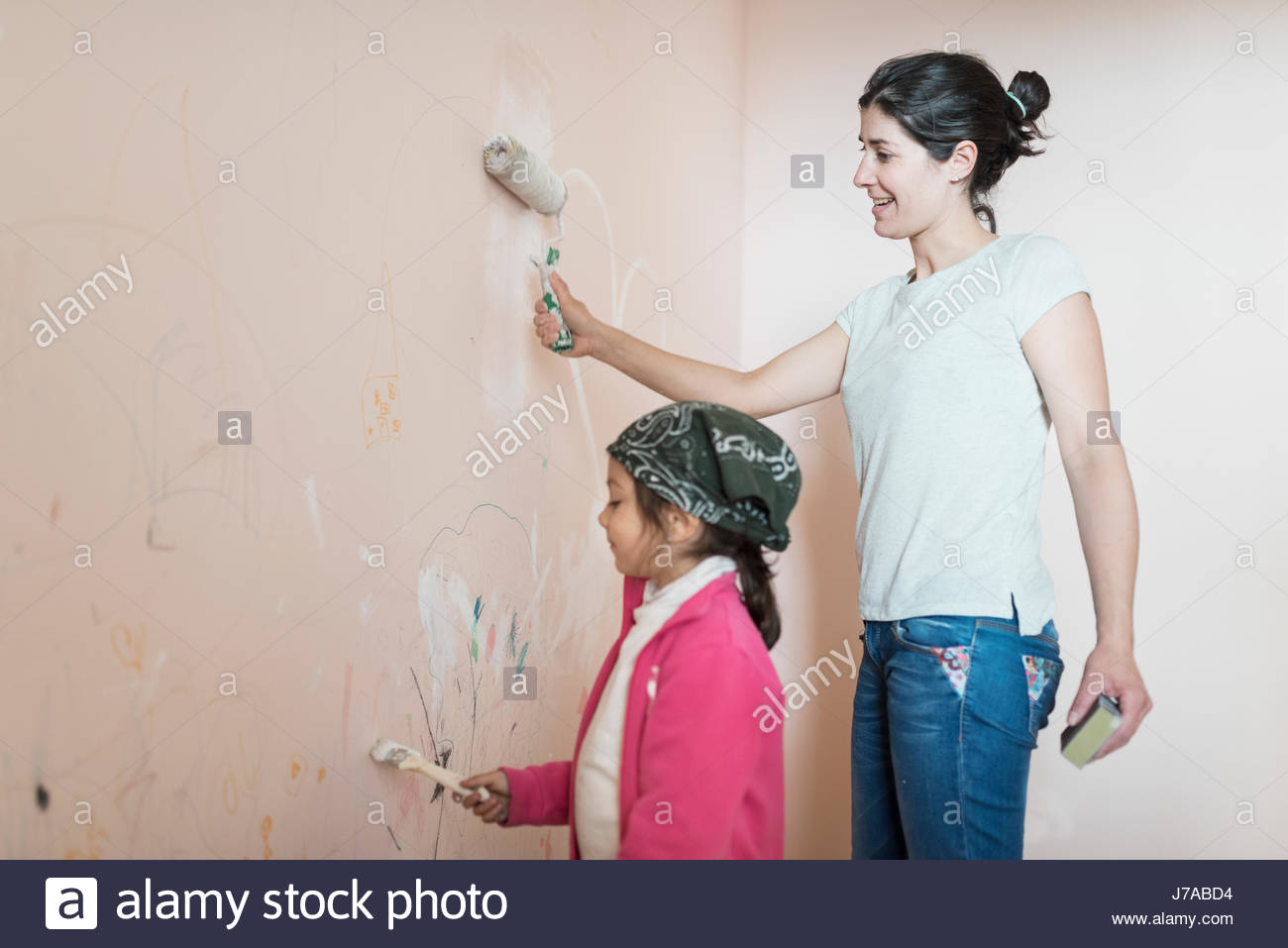 Mother And Daughter Painting Wall In Children S Room Stock Photo